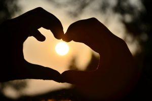 Coeur dessiné avec les mains devant un coucher de soleil.