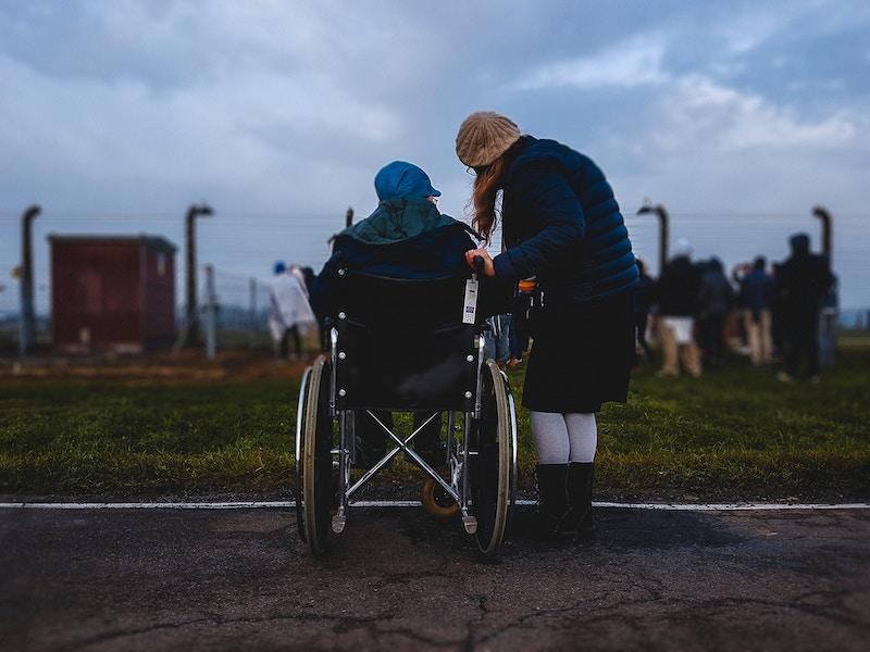 une personne en fauteuil roulant accompagné d'une baluchonneuse