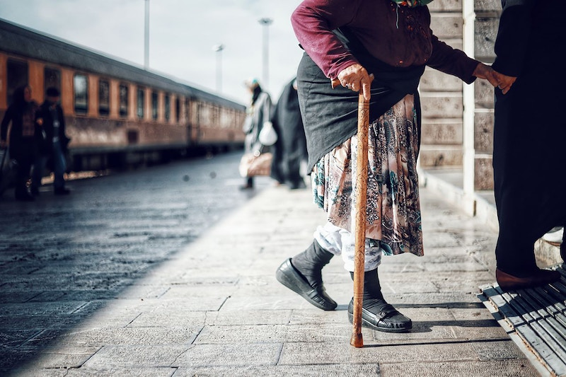 senior avec une canne à la gare