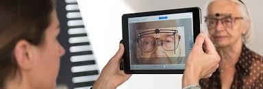 l'opticien à domicile analyse la vision d'une patiente à l'aide d'un outil numérique adapté