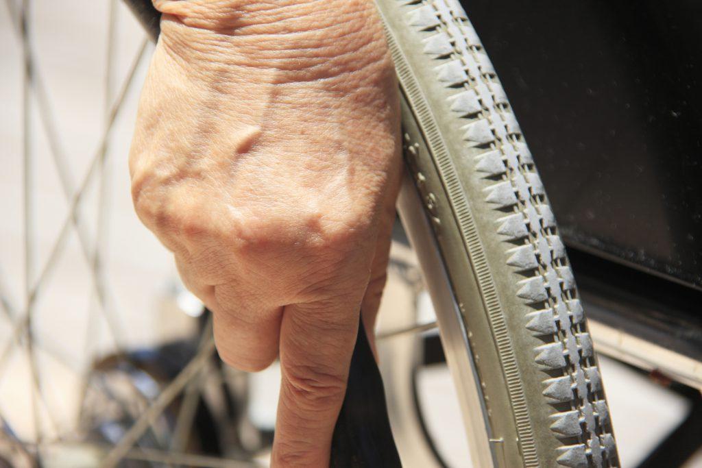 Une main de femme sur une roue de fauteuil-roulant