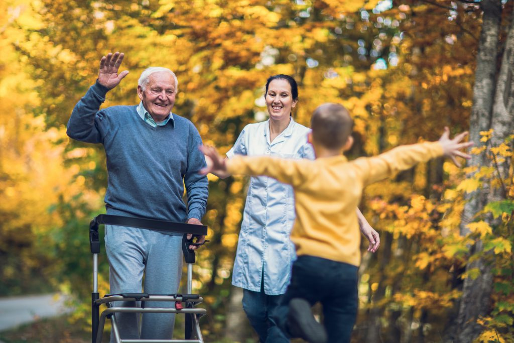 Grand-père qui retrouve son petit-fils, accompagné par une aidante.