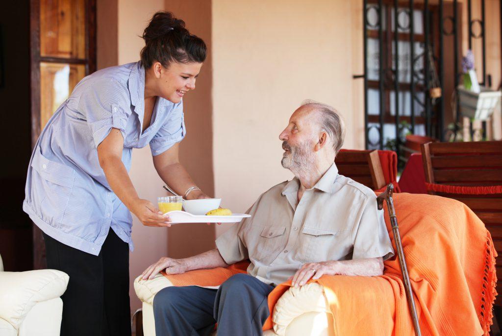 personne âgée dans un fauteuil qui se fait aider pour son repas.