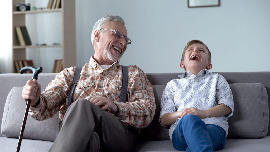 Grand-père et son petit fils ensemble assis dans un canapé