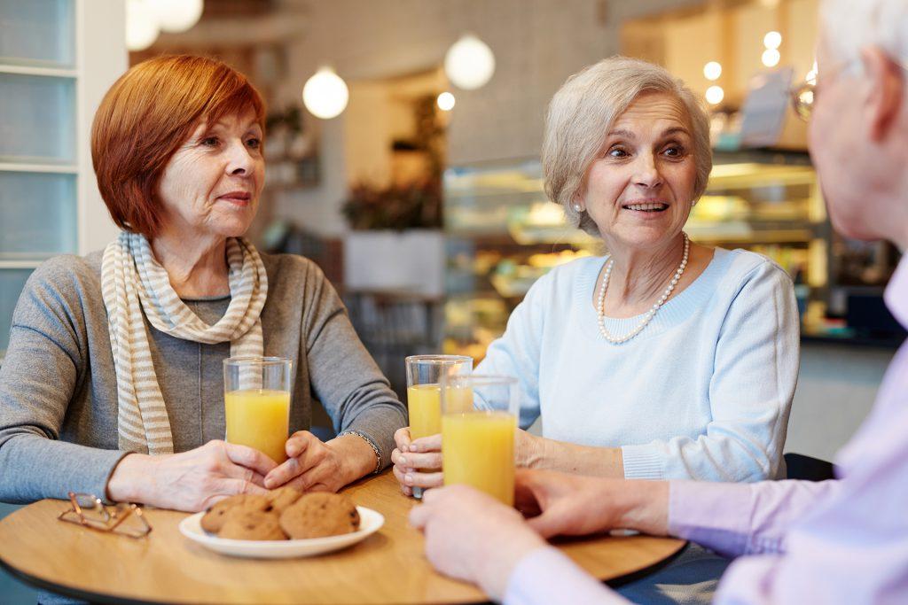 Trois amis discutent ensemble autour d'un encas dans un café