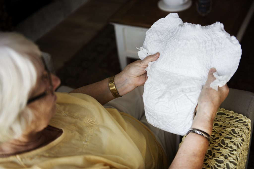 Une femme âgée tient dans ses mains une culotte absorbante dans un intérieur sombre. On ne vois pas la femme en entier, on a une vision de la scène par dessus son épaule.