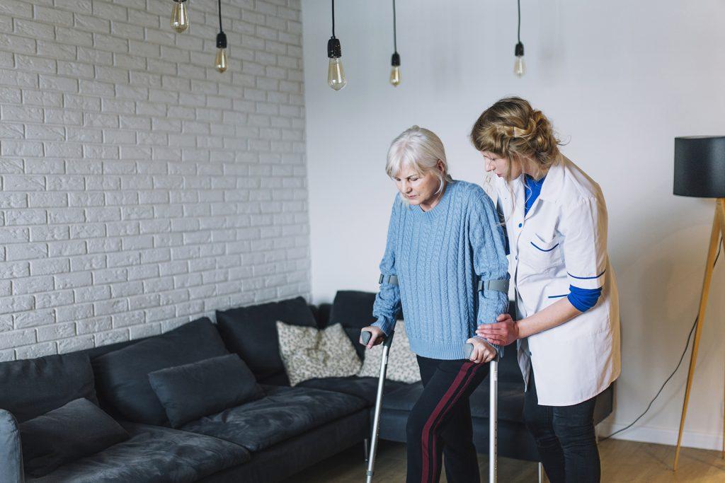 Infirmière qui accompagne une femme âgée qui éprouve des difficultés pour se déplacer