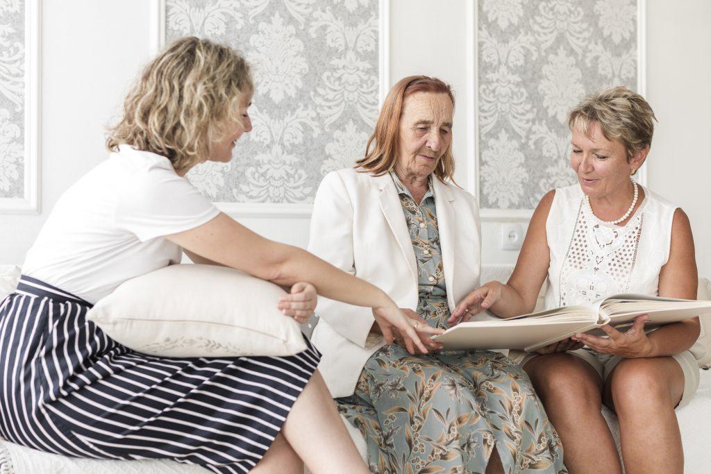 Una abuela con su hija y su nieta, están mirando un libro abierto.