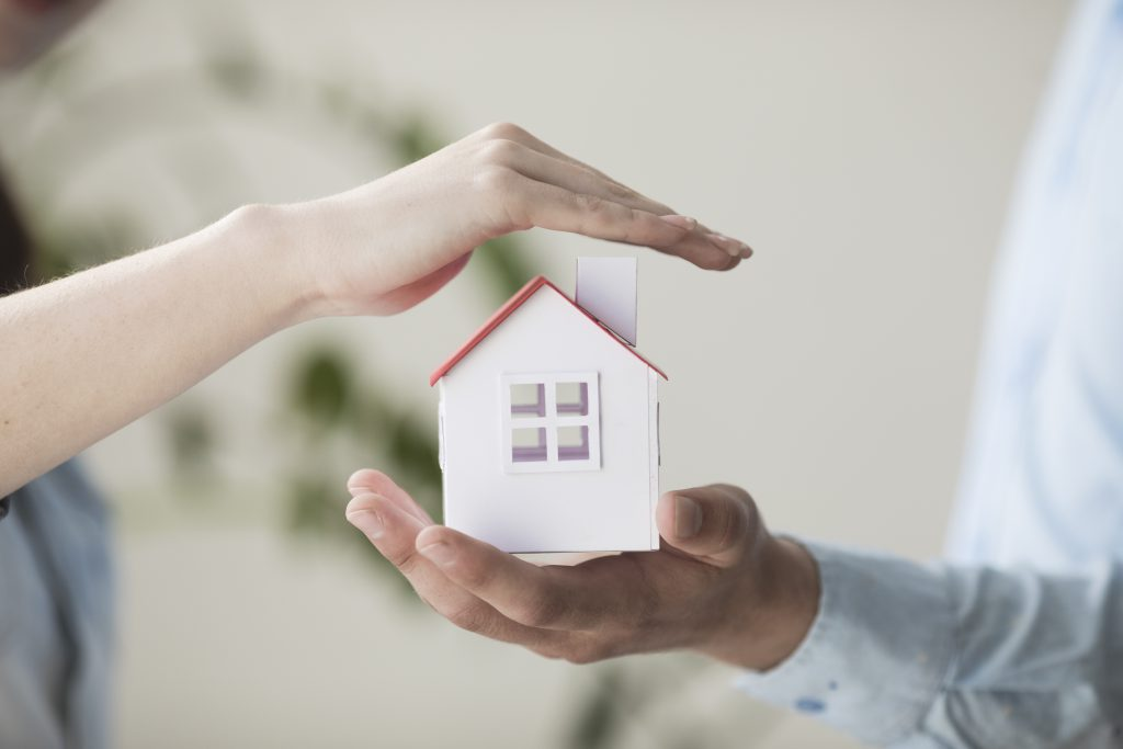 dos manos que muestran una casa