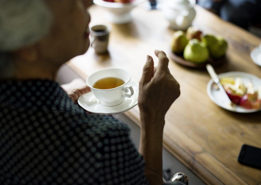 Personne âgée assise à table le temps d'une pause thé