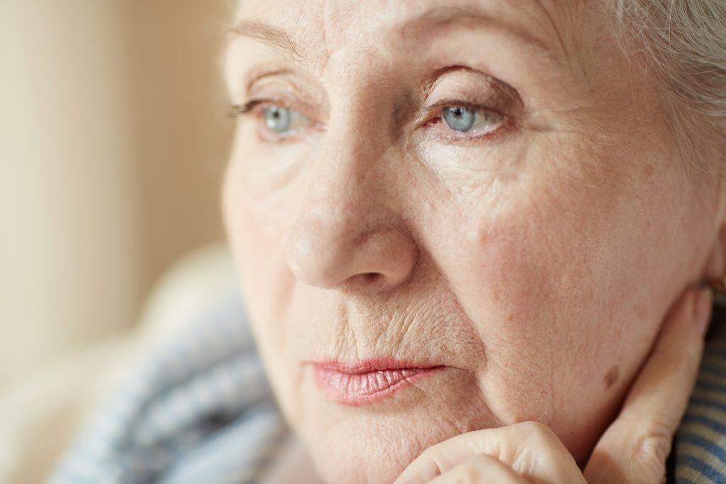 Gros plan visage d'un femme âgée pensive