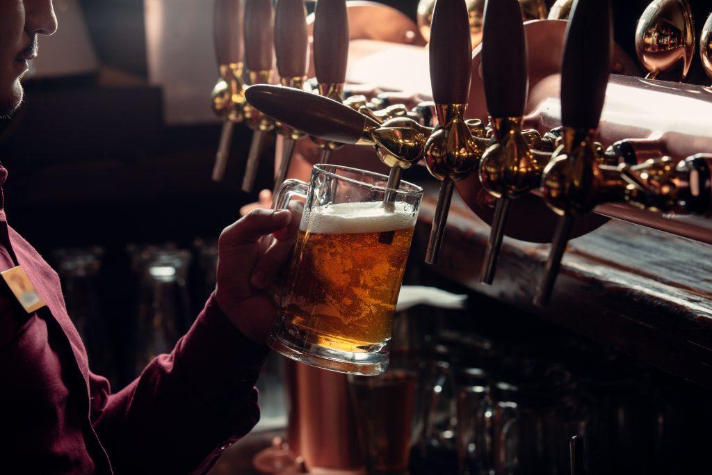 Serveur d'un bar remplissant un verre de bière