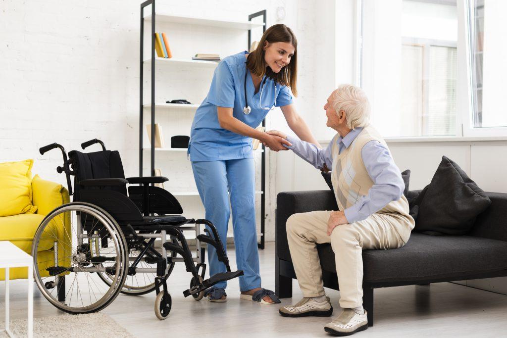 Aide-soignante aide une personne âgée à se mettre dans son fauteuil roulant.