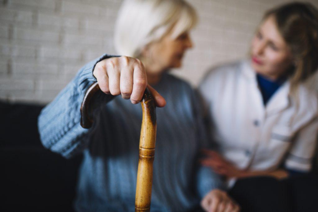 Une aide soignante parle avec une femme qui tient une canne.