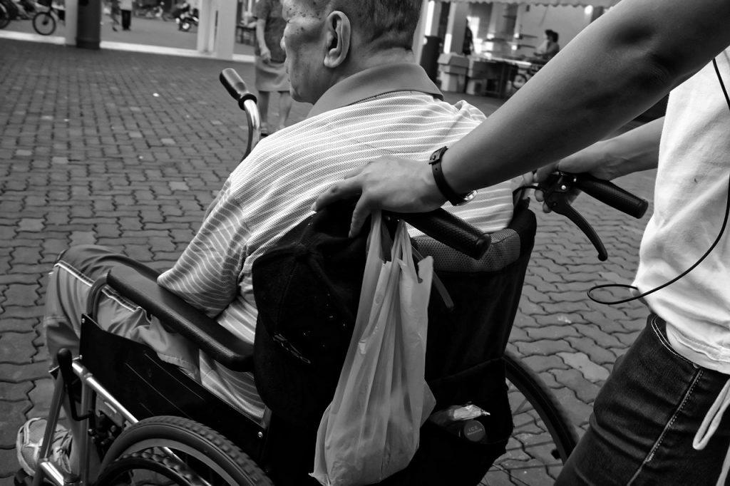 Homme en fauteuil roulant aidé par un proche