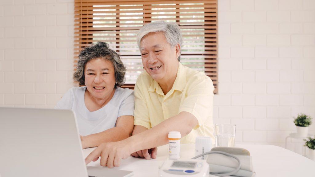 Pareja de ancianos asiáticos usando una computadora portátil conferencia con el médico sobre la información de la medicina en la sala de estar, pareja usando el tiempo juntos mientras están acostados en el sofá de la casa. Concepto de salud familiar en el hogar.