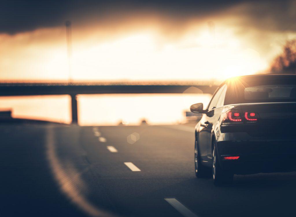 Une voiture qui roule sur une route ensoleillé