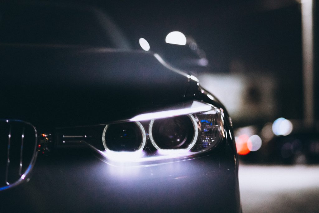 Devant d'une voiture avec les feux allumé, la nuit