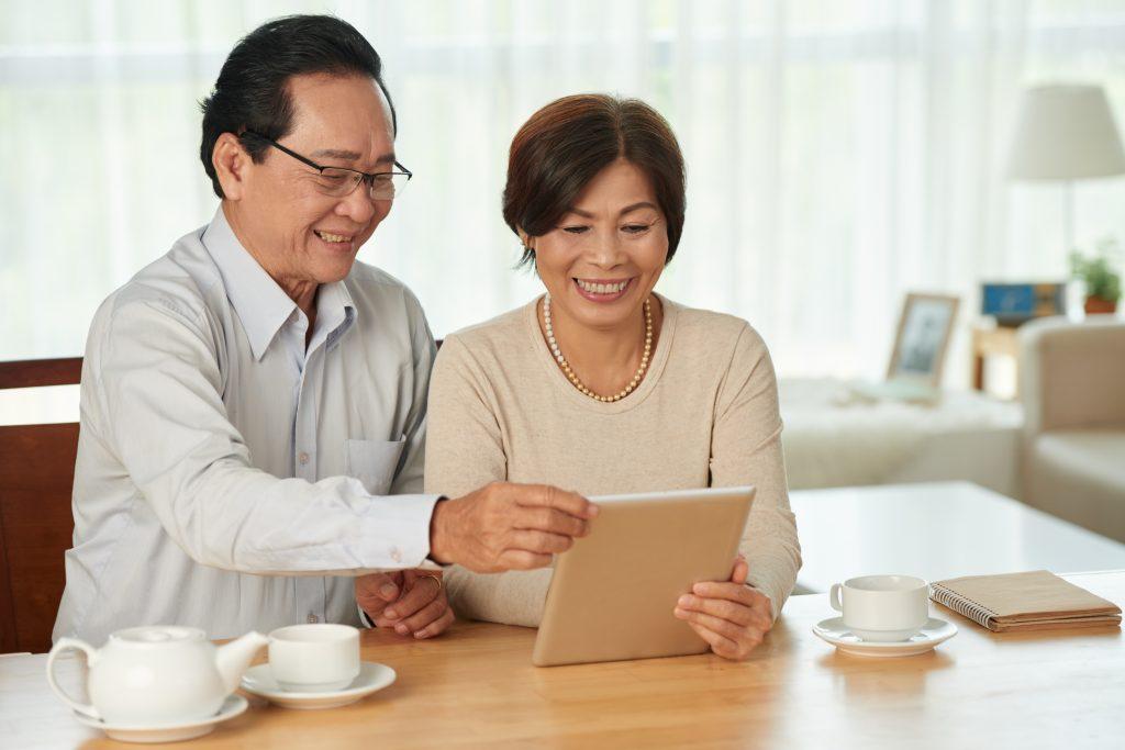 Alegre pareja de ancianos tomando té y viendo algo en la computadora de la tableta en su sala de estar.