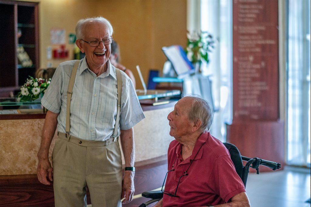 Deux seniors plaisantent ensemble dans l'entrée d'une maison de retraite.