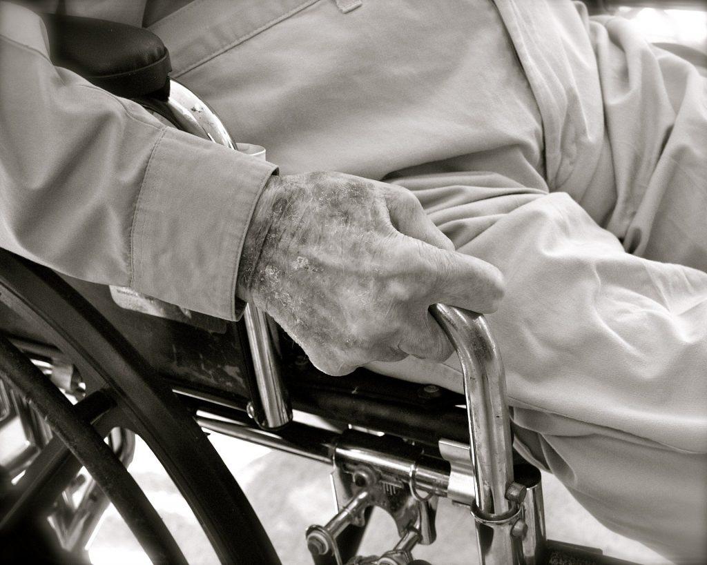 Zoom sur la main d'un personne âgé dans un fauteuil en noir et blanc qui a probablement subi de la maltraitance.