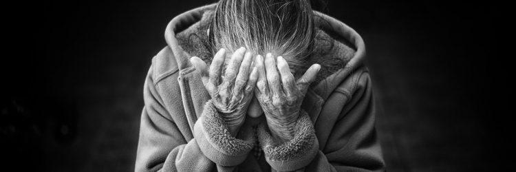 Personne âgée qui subit de la maltraitance et qui se tiens la tête dans les mains.