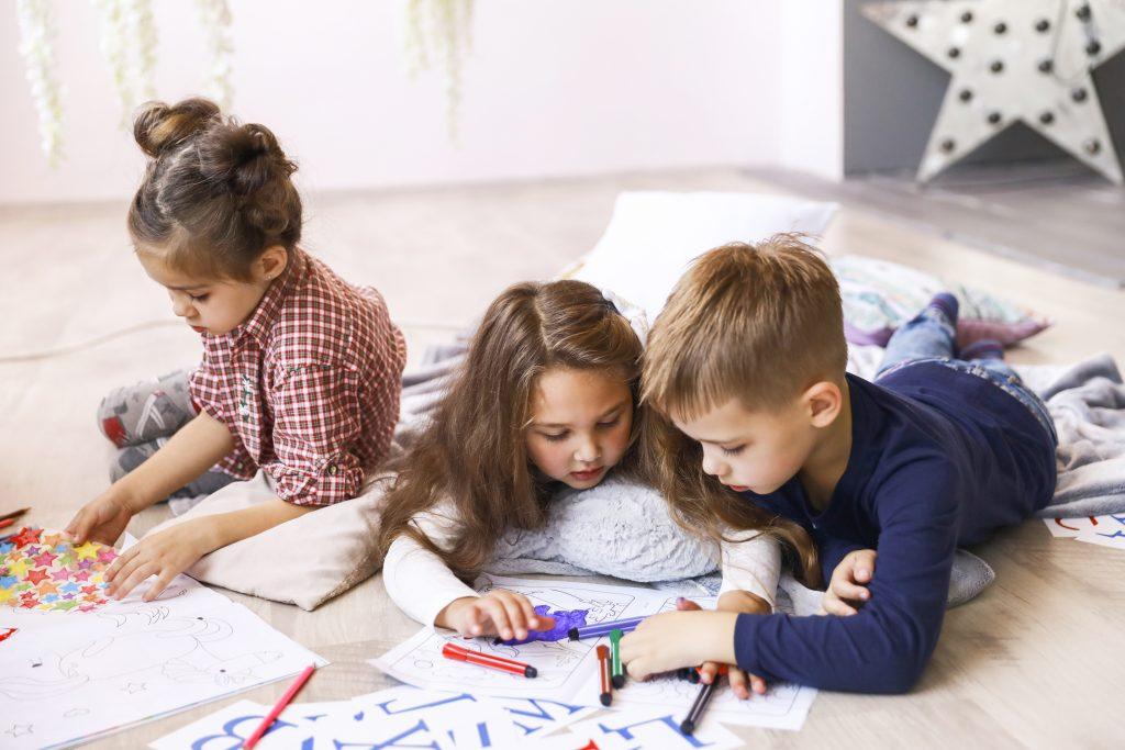 Tres niños concentrados están jugando en el suelo y dibujando en libros para colorear.