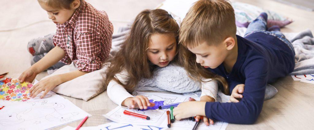 Trois jeunes enfants dessinent ensemble