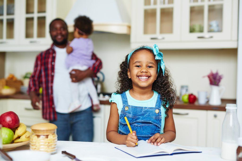 Una joven feliz mirando a la cámara mientras esta escribiendo en la cocina.