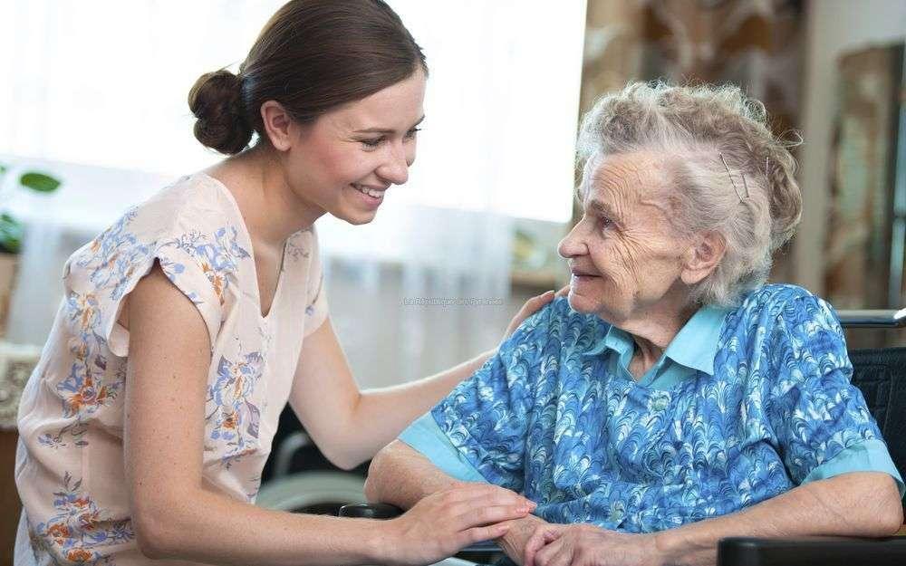 Jeune femme qui aide une personne âgée.