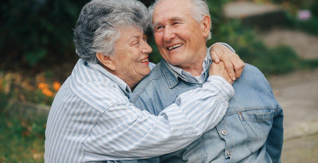 Una pareja de ancianos en un parque. Abuelos abrazándose.
