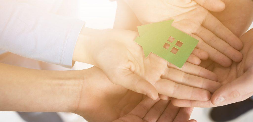Muchas manos con una casa en papel al medio de las manos.