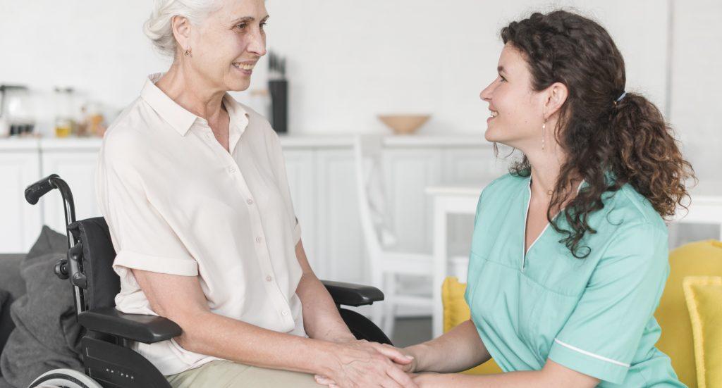 Una abuela con una cuidadora, sonriéndose
