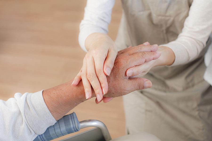 Deux mains entrelacées, celle d'une personne âgée et celle d'une personnes plus jeune.