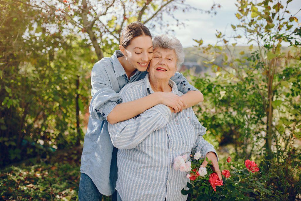 Una anciana con una flor en la mano. Mujer con una camisa azul. La abuela con la nieta.