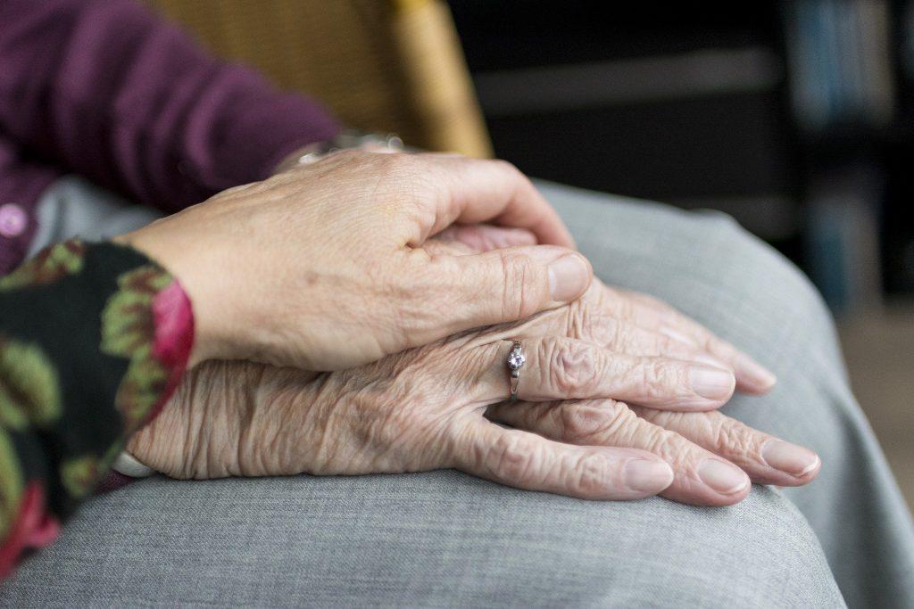 dos personas, dándose las manos sobre rodillas.